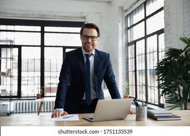 Portrait of smiling confident young Caucasian businessman in glasses posing in modern office, happy successful male boss or director in formal suit look at camera, show success confidence at workplace