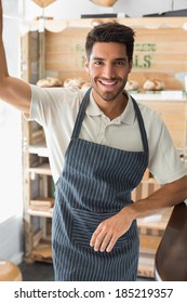 Portrait of a smiling confident young male barista standing at the coffee shop