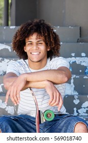 Portrait of smiling cool guy sitting outside with skateboard