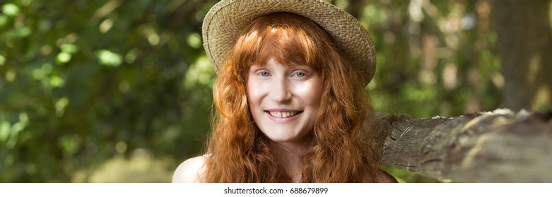 Portrait of smiling country girl in summer hat