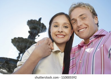 Portrait of smiling couple with arms around standing in front of fountain
