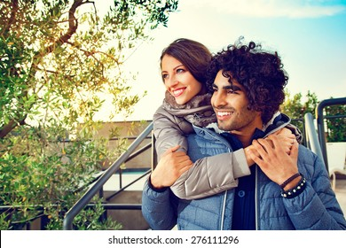 Portrait of Smiling Couple with Arms Around Each Other Outdoors and Looking to the Side