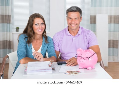 Portrait Of A Smiling Couple Calculating Bills At Home