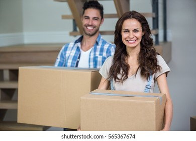 Portrait of smiling couple with cardboard boxes standing in new house