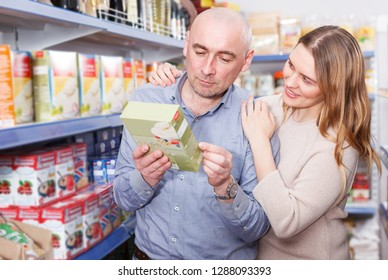 Portrait of smiling couple  customers choosing groats in  supermarket