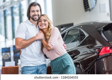 portrait of smiling couple at dealership salon
