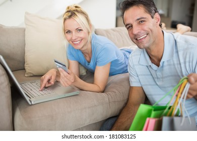 Portrait of a smiling couple doing online shopping through computer and credit card at home