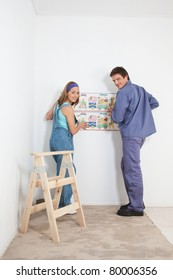 Portrait of smiling couple hanging baby wallpaper