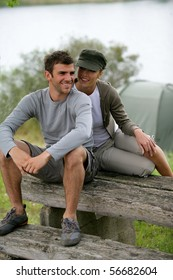 Portrait of a smiling couple of hikers sitting on a table