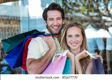 Portrait of smiling couple holding shopping bags at shopping mall