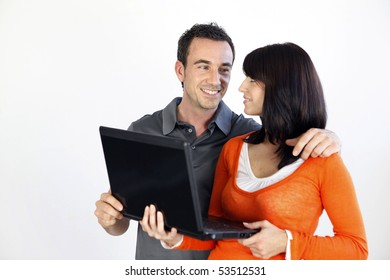 Portrait of a smiling couple with a laptop computer on white background