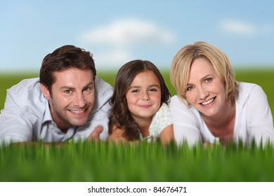 portrait of smiling couple and little daughter lying on grass