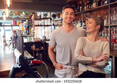 Portrait Of Smiling Couple Owning Bar Standing Behind Counter