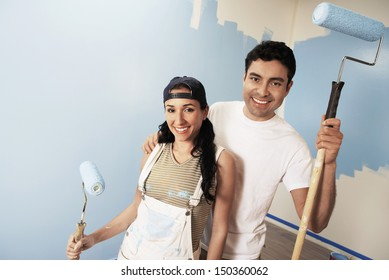 Portrait of smiling couple with paint rollers standing against partially painted wall