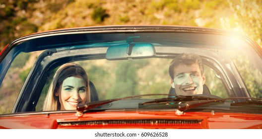 Portrait of smiling couple in red cabriolet during sunny day