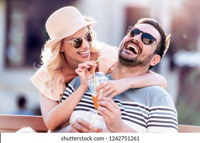 Portrait of smiling couple sitting on the bench and drink juice.