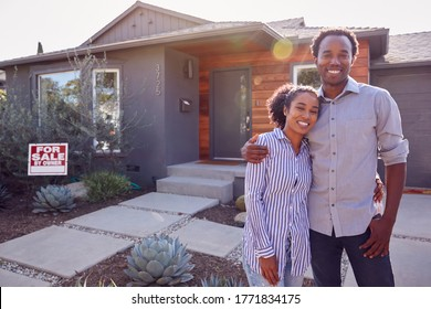 Portrait Of Smiling Couple Standing Outdoors In Front Of House With For Sale Sign In Garden
