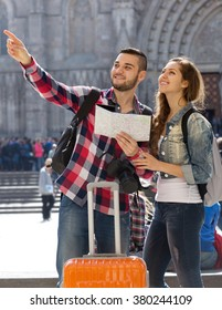 Portrait smiling couple of travellers with map at street