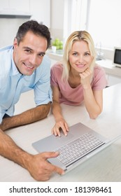 Portrait of a smiling couple using laptop in the kitchen at home