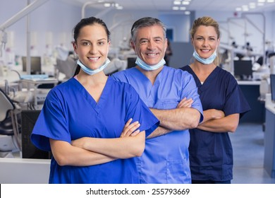 Portrait of smiling co-workers in a line with arms crossed in dental clinic