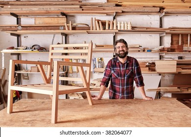 Portrait of a smiling craftsman with a rugged beard, resting on his workbench with a wooden chair frame on it, looking at the camera, with shelves of wooden planks and pieces behind him