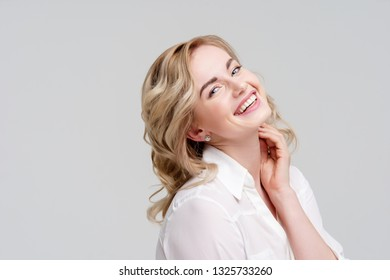Portrait of smiling curly blonde in white shirt.