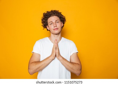 Portrait of a smiling curly haired man praying isolated over yellow background