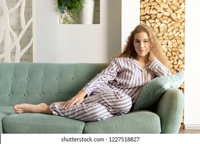 Portrait of smiling curly woman laying on sofa in cozy pyjamas. Sweet young woman enjoying lazy morning at home. Modern interior happiness and lifestyle concept