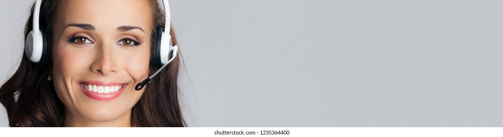 Portrait of smiling customer support phone operator in headset, empty copy space place for slogan or some advertising text message, over grey background. Call center and customer support service.