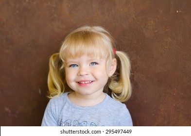 portrait of smiling cute funny blonde girl on brown wall background
