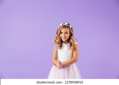 Portrait of a smiling cute pretty girl dressed in a princess dress isolated over violet background, holding magic wand