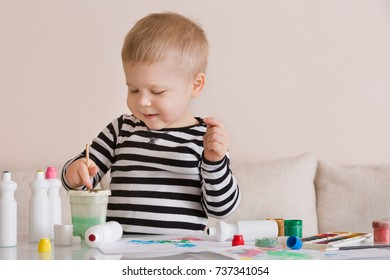 Portrait of smiling cute toddler boy drawing at home with color paints and brush. Creative child having fun. Educational and learning concept