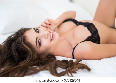 Portrait of a smiling cute woman in lingerie lying on the bed and looking at camera