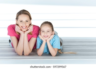 portrait of smiling daughter and mother after training on white