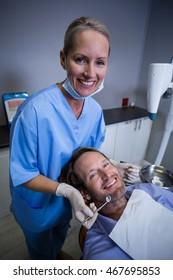 Portrait of smiling dentist examining a young patient with tools in dental clinic