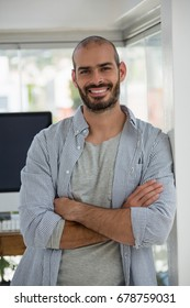 Portrait of smiling designer with arms crossed leaning on wall in office