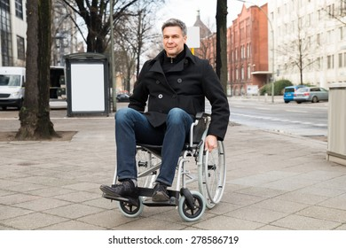 Portrait Of A Smiling Disabled Man On Wheelchair In City