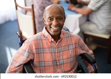 Portrait of smiling disabled senior man sitting on wheelchair at retirement home