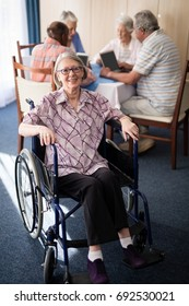 Portrait of smiling disabled senior woman sitting on wheelchair against friends at retirement home