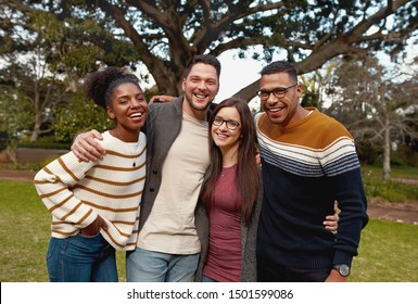 Portrait of a smiling diverse group of young friend enjoying in the park - colorful clothing - very happy