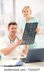 Portrait of smiling doctor and nurse holding x-ray image in office.?