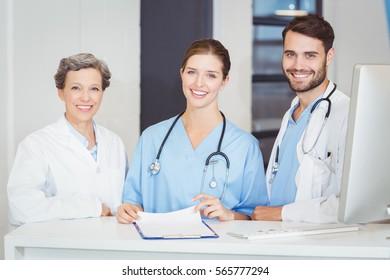 Portrait of smiling doctor team standing at computer desk in hospital
