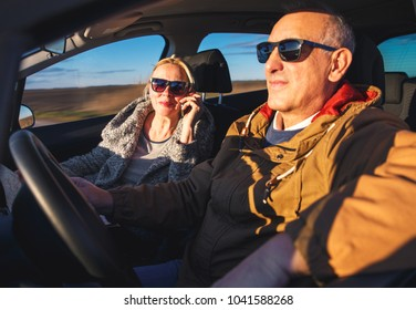 Portrait of smiling elderly couple driving car, while female passenger talking on phone.