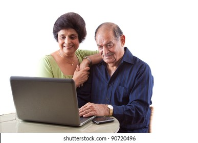 Portrait of a smiling elderly East Indian couple on computer laptop