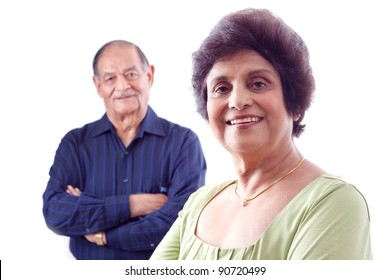 Portrait of a smiling elderly East Indian woman with her husband in the background