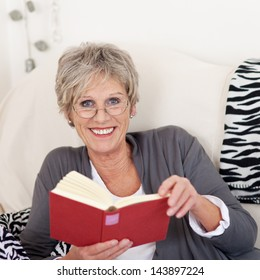 Portrait of a smiling elderly female reading a book and giving a beautiful smile.