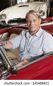 Portrait of smiling elderly man sitting in car in shop