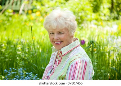 Portrait of the smiling elderly woman in  a garden