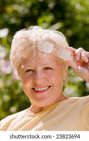 Portrait of the smiling elderly woman in the glasses