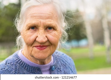 Portrait of a smiling elderly woman. A photo on the nature background